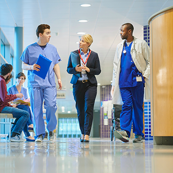 Healthcare providers discussing their network participation while walking the hallway